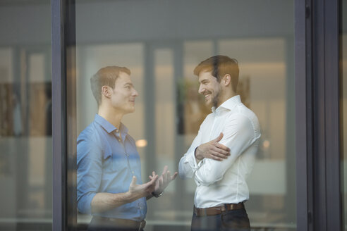 Two businessmen communicating behind window in an office - SHKF000162