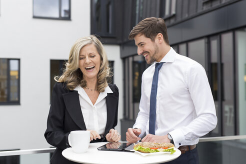 Laughing businessman and businesswoman having lunch break - SHKF000178
