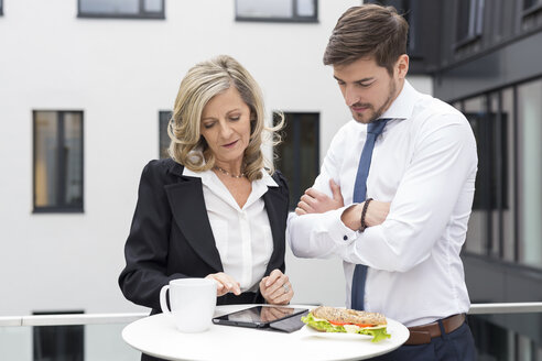 Businessman and businesswoman having lunch break with digital tablet - SHKF000180