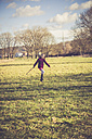 Little girl jumping on a meadow - SARF001235