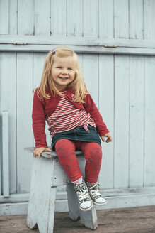 Little girl sitting on a stool in front of a wooden wall - IP000178