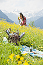 Young woman picking flowers on alpine meadow - HHF005034