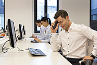 Frustrated man at desk with colleagues in background - SHKF000222