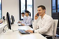 Man at desk on cell phone with colleagues in background - SHKF000223