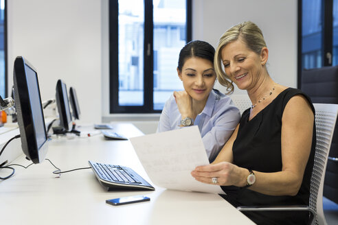 Two businesswomen with paper talking at desk - SHKF000206