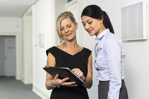 Two businesswomen with digital tablet on office floor - SHKF000207