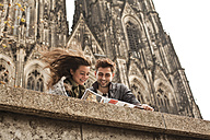 Germany, Cologne, young couple watching city map in front of Cologne Cathedral - FEXF000236