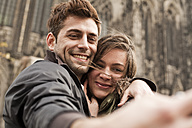 Germany, Cologne, young couple taking selfie in front of Cologne Cathedral - FEXF000239