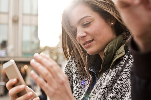 Germany, Cologne, young woman using smartphone - FEXF000242
