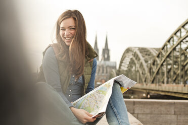 Germany, Cologne, portrait of smiling young woman with city map on knee - FEXF000257