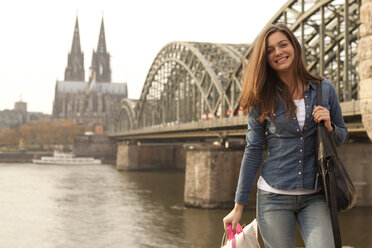 Germany, Cologne, smiling young woman with shopping bags in front of Hohenzollern Bridge - FEXF000260