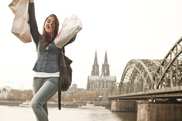 Germany, Cologne, happy young woman with shopping bags - FEXF000263