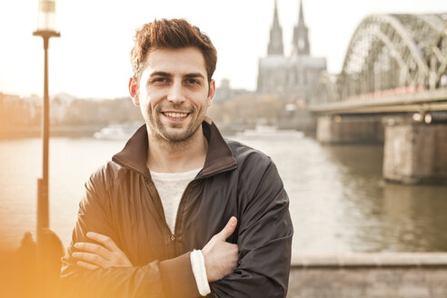 Germany, Cologne, portrait of smiling young man - FEXF000266