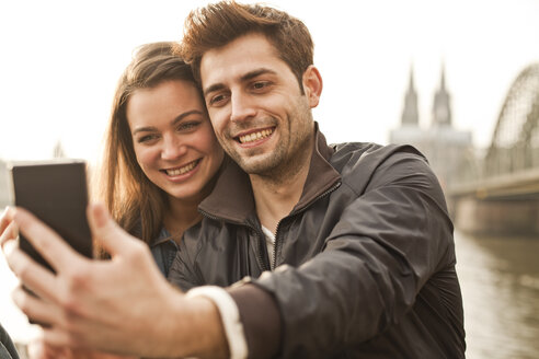 Germany, Cologne, young couple taking selfie - FEXF000275