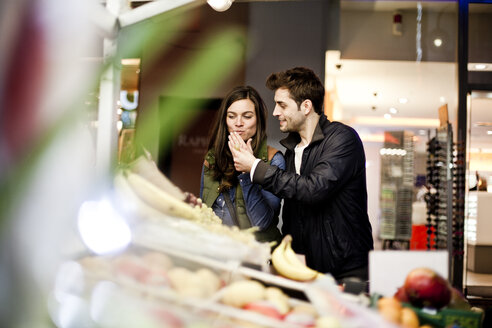 Germany, Cologne, young couple  tasting fruits at grocery stand - FEXF000281