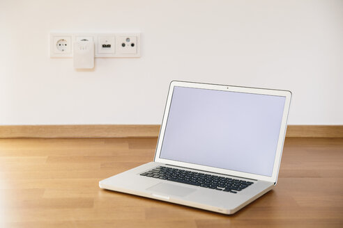 Laptop standing on wooden flooring in front of WiFi extender - MFF001383