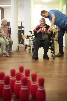 Geriatric nurse talking to age demented senior woman with foam ball in a nursing home - DHL000504