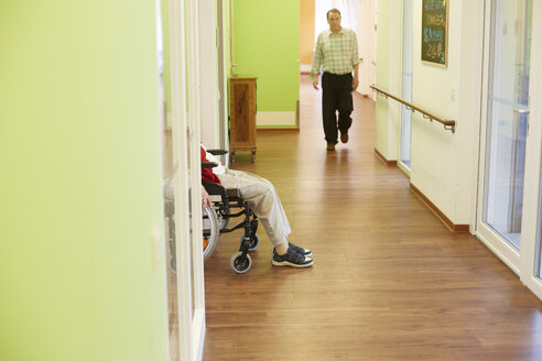 Age demented senior man walking on corridor in a nursing home - DHL000524