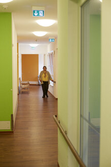 Age demented senior woman on corridor in a nursing home - DHL000521