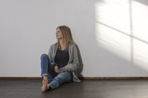 Young daydreaming woman sitting on floor - LAF001276