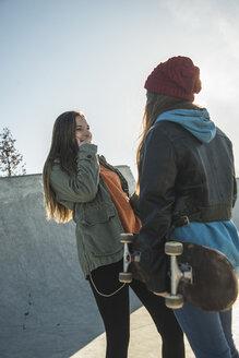 Two teenage girls in skatepark talking - UUF003080