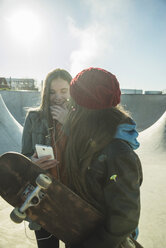 Two happy teenage girls with cell phone in skatepark - UUF003082