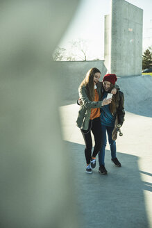 Two happy teenage girls with cell phone in skatepark - UUF003061