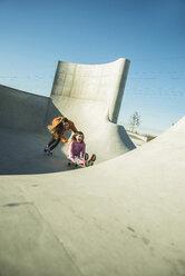 Teenage girl pushing girl on skateboard - UUF003085