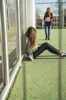 Two teenage girls on sports ground - UUF003071