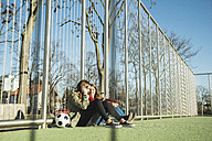Two teenage girls on sports ground sharing cell phone - UUF003073