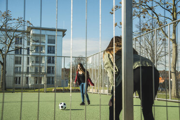 Two teenage girls on sports ground playing soccer - UUF003074