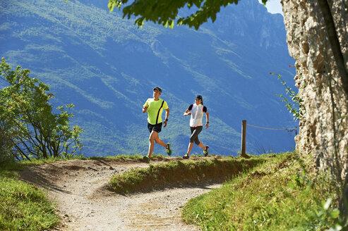 Italy, Trentino, couple running near Lake Garda - MRF001467