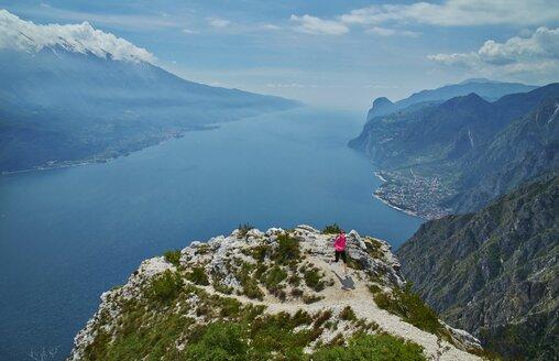 Italy, Trentino, woman running on mountain peak at Lake Garda - MRF001495