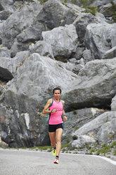 Italy, Trentino, woman running on road near Lake Garda - MRF001513