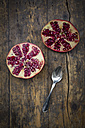 Two halves of a pomegranate and tea spoon on wood - LV002621