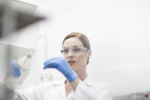 Scientist in lab working with liquid - ZEF004229