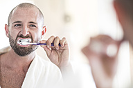 Mirror image of man brushing his teeth - ZEF003145