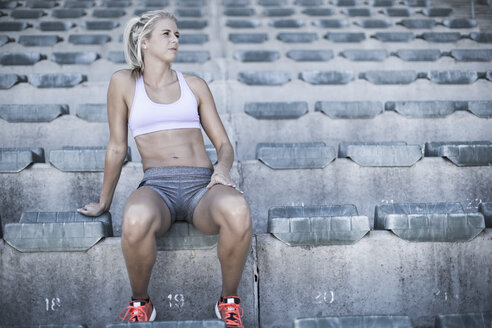 Portrait of sportswoman sitting on grandstand of a stadium - ZEF004591