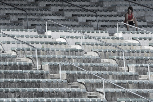 Young sportsman sitting on grandstand of a stadium - ZEF004597