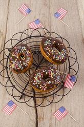 Three American cronuts with chocolate icing and sugar confetti - ODF001052