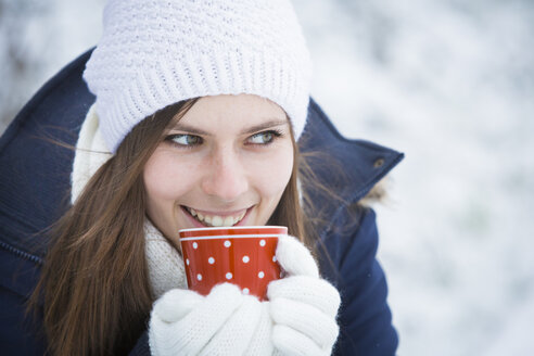 Portrait of smiling young woman with cup in winter - JTLF000047