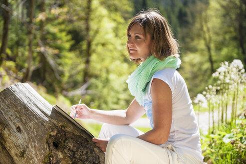 Austria, Altenmarkt-Zauchensee, woman drawing in the nature - HHF005067