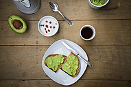 Bread with avocado cream, yogurt with pomegranate seeds and cup of coffee - LVF002656