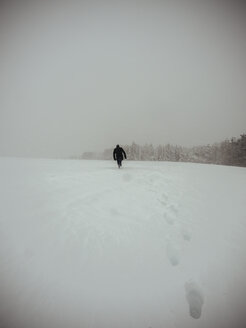 Germany, Black Forest, man walking in snow, in stormy weather - KRP001261