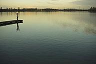 Germany, Roxheim, woman standing on wooden boardwalk at water - UUF003089