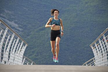 Italy, Trentino, woman jogging on bridge at Lake Garda - MRF001523