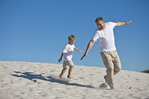 Playful father and son in sand - ZEF004768