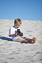 Happy boy sitting on a sandy beach looking at camera - ZEF004892