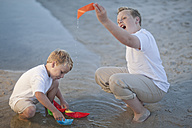 Two boys playing with paper boats at a water pool on a sandy beach - ZEF004787
