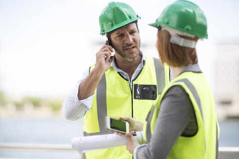 Manager and foreman discussing construction project on site - ZEF003839